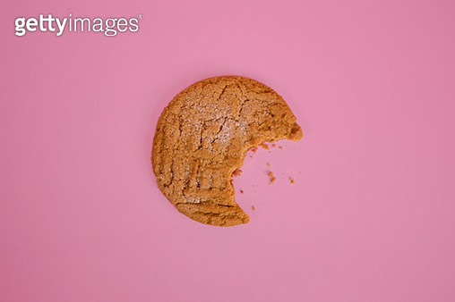 Homemade vegan, gluten free peanut butter cookie with bite missing on pink background - gettyimageskorea