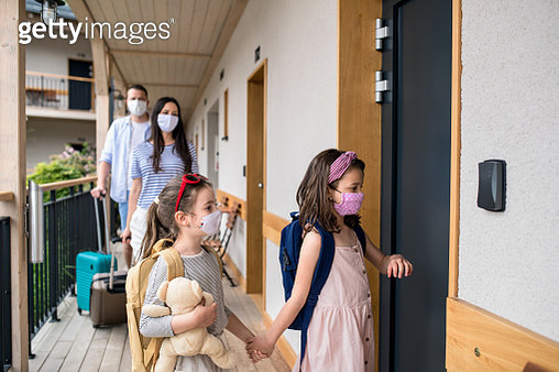 Family with children and face masks outdoors by hotel in summer, holiday concept. - gettyimageskorea