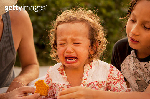 Crying child at picnic table, others comforting - gettyimageskorea