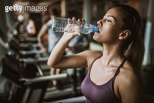 Thirsty female athlete drinking fresh water on a break in a gym. - gettyimageskorea