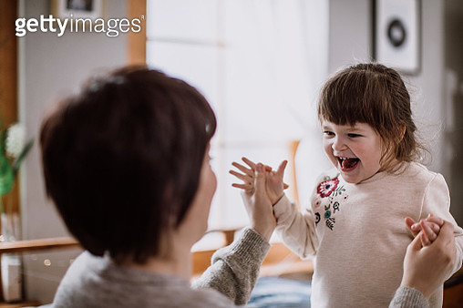 Mother having fun with her little daughter on bed - gettyimageskorea