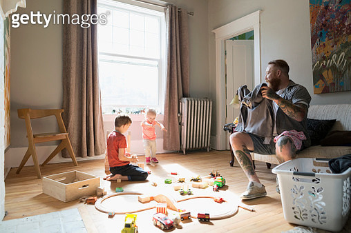Father folding laundry near children playing with toy train and wood blocks - gettyimageskorea