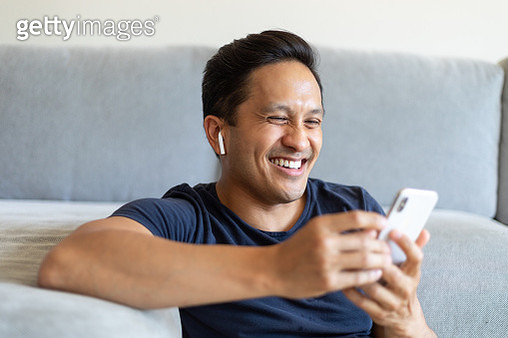 Man smiling during a video call on his cell phone at home - gettyimageskorea