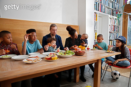 Large multi ethnic family having food at kitchen table - gettyimageskorea