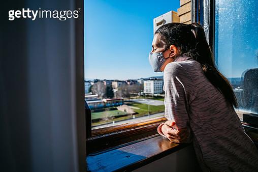 Woman in quarantine looking through the window - gettyimageskorea