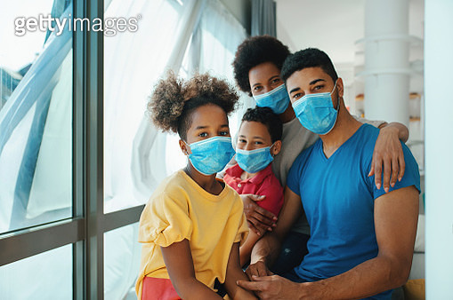 Closeup side top view of an african american and hispanic family wearing face masks and staying at home. They are sitting next to the window and talking,parents providing support for the kids by talking and calming them. All looking at camera. - gettyimageskorea