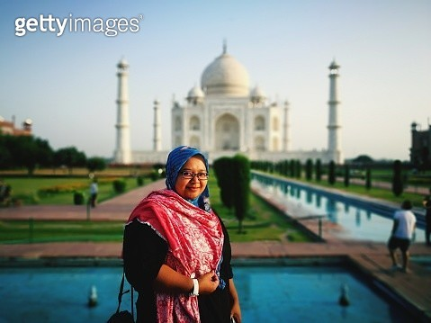 Portrait Of Smiling Woman Standing Against Taj Mahal - gettyimageskorea
