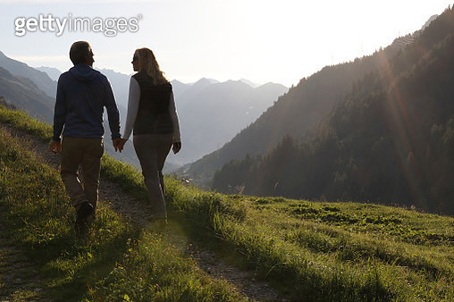 Couple follow grassy track above mountain ranges - gettyimageskorea