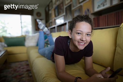 Portrait smiling, confident tween girl with smart phone on sofa - gettyimageskorea
