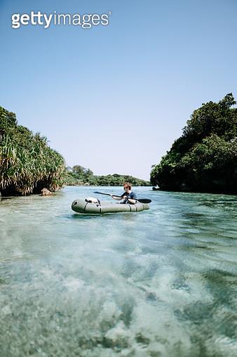 Man paddling a packraft on clear tropical lagoon water, Ishigaki Island of the Yaeyama Islands, Okinawa, Japan - gettyimageskorea