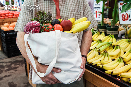 Close up of person at a food and vegetable market, holding shopping bag with fresh produce including bananas, tomatoes and cabbage. - gettyimageskorea