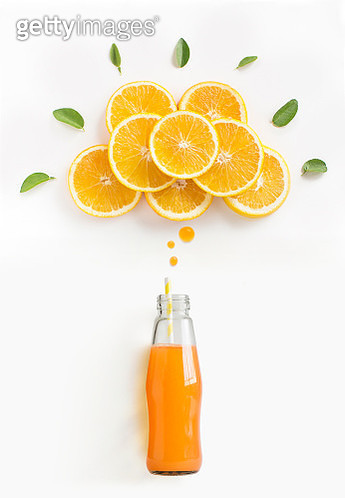 Orange juice in bottle with speech bubble formed by slices of orange. Conceptual graphical stylised food still life photography. - gettyimageskorea