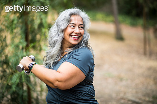 A beautiful senior Mexican Woman working out and stretching with weights - gettyimageskorea