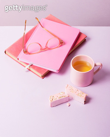 Books, tea, nougat and glasses in a pastel setting. - gettyimageskorea
