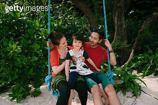 Japanese father, Caucasian mother and mixed race daughter having fun on swing, Ishigaki Island, Okinawa, Japan - gettyimageskorea