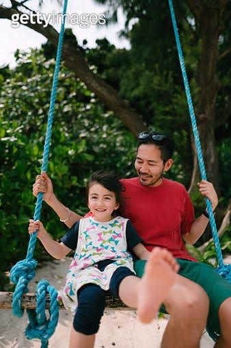 Japanese father and his mixed race 4 year old girl having fun on swing on beach, Ishigaki Island, Okinawa, Japan - gettyimageskorea