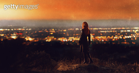 Back view of woman with long red hair wearing black coat and heeled boots standing on hillside looking at sunset over valley of city lights - gettyimageskorea