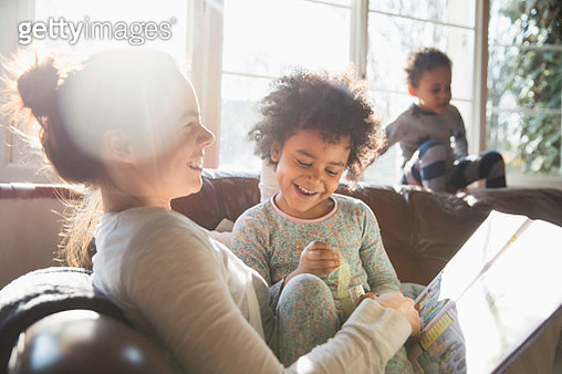 Happy mother and daughter cuddling, reading book on sofa in sunny living room - gettyimageskorea