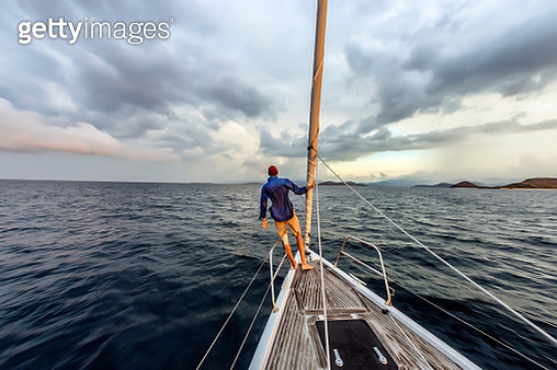 Rear view shot of single man standing on bow of yacht, Lombok, Indonesia - gettyimageskorea