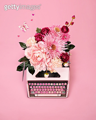 Overhead view of vintage pink typewriter with candy heart keys and flowers, butterflies, and hearts spilling from paper return on pink background. - gettyimageskorea