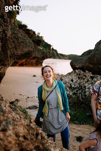 Caucasian woman laughing while walking on tropical beach at sunset, Ishigaki Island of the Yaeyama Islands, Okinawa, Japan - gettyimageskorea