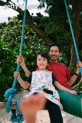 Japanese father and his mixed race 4 year old child having fun on swing on beach, Ishigaki Island, Okinawa, Japan - gettyimageskorea