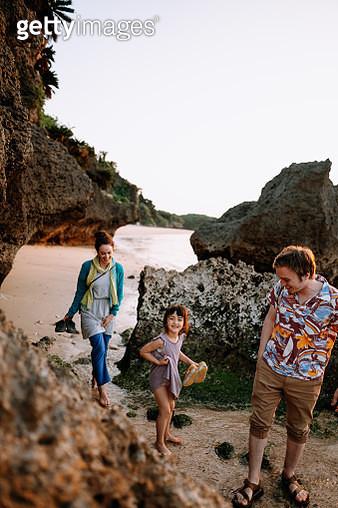 Family smiling and walking on tropical beach at sunset, Ishigaki Island of the Yaeyama Islands, Okinawa, Japan - gettyimageskorea