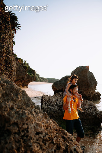 Father carrying his little girl on shoulders and walking on beach at sunset, Ishigaki Island of the Yaeyama Islands, Okinawa, Japan - gettyimageskorea