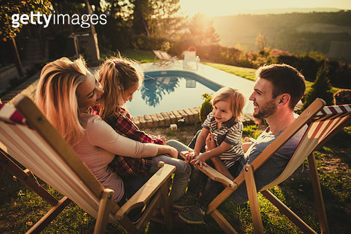 Happy family communicating in deck chairs at the back yard. - gettyimageskorea