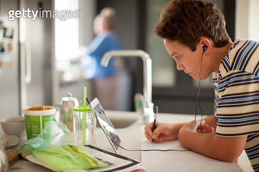 Young student working on digital tablet in his kitchen during lockdown - gettyimageskorea