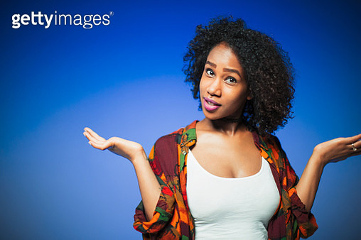 Portrait young woman shrugging - gettyimageskorea