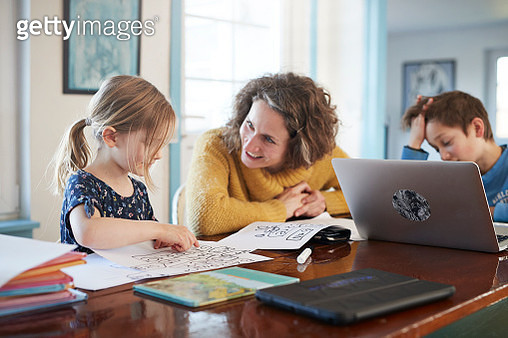 Mother homeschooling daughter and son at table - gettyimageskorea