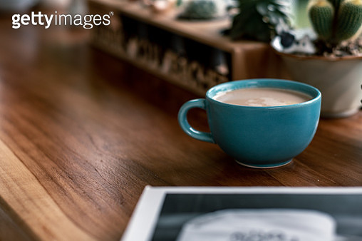 Close-Up Of Coffee Cup With Potted Plant On Wooden Table - gettyimageskorea