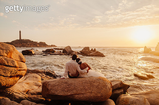 Rear View Of Couple Sitting At Beach Against Sky - gettyimageskorea