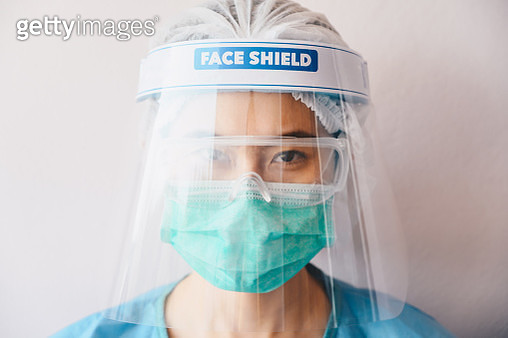 Portrait of healthcare worker while wearing medical scrubs, mask and face shieldl before working in hospital during Covid-19 pandemic. - gettyimageskorea