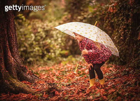 Happy child girl with an umbrella and rubber boots - gettyimageskorea