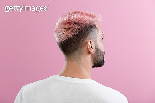 The back of a man's head, tilted to the right, with pink hair, taken in front of a pink backdrop. - gettyimageskorea