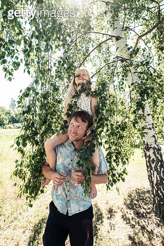 Father carrying daughter piggyback under a birch tree - gettyimageskorea