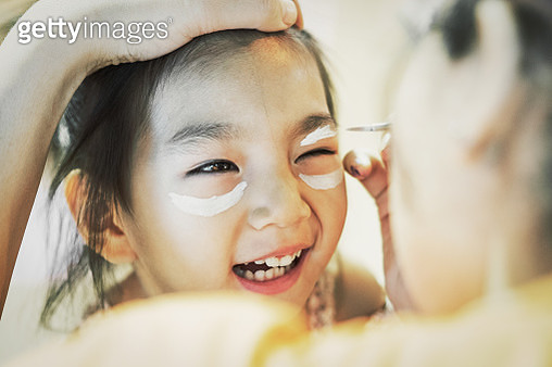 Mother painting face of her daughter for Halloween party - gettyimageskorea