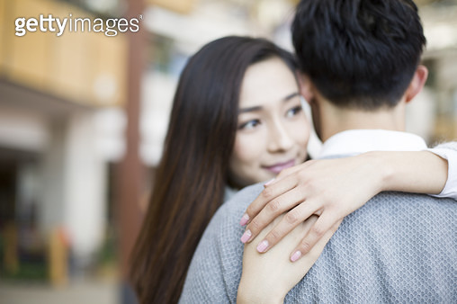 Young couple embracing in shopping mall - gettyimageskorea
