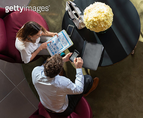 Business couple at a hotel lounge in a meeting looking at some graphs on tablet - gettyimageskorea