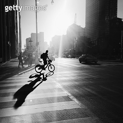 Silhouette Of Man With Bicycle In City - gettyimageskorea