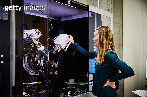 Female scientist preparing to work with X-ray photoelectron spectroscopy machine - gettyimageskorea