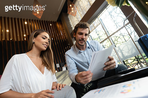 Business couple in a meeting at a hotel lounge looking at some documents smiling - gettyimageskorea
