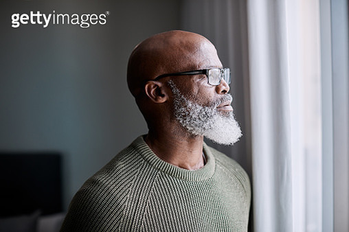 Shot of a mature man looking thoughtfully through a window at home - gettyimageskorea