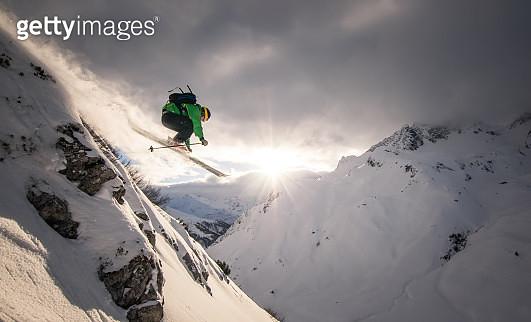 Austria, Freeride skier jumping off rock - gettyimageskorea