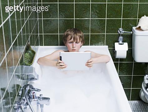boy in a bubble bath using digital tablet - gettyimageskorea