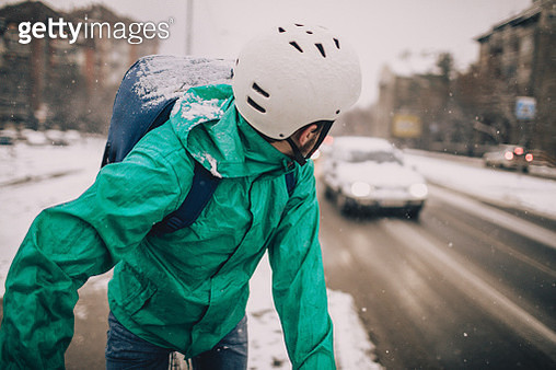 Delivery man on a bike in a snowy day - gettyimageskorea