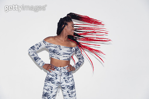 Carefree young woman in camouflage clothing flipping hair - gettyimageskorea