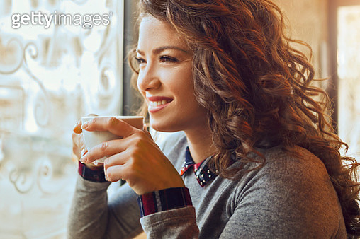 Pretty woman enjoin coffee and smiling - gettyimageskorea